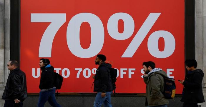FILE PHOTO: Pedestrians pass a sale sign on a retail shop on Oxford Street in London