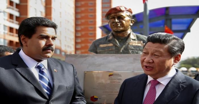 FILE PHOTO: China's President Xi speaks with Venezuela's President Maduro in front of a statue