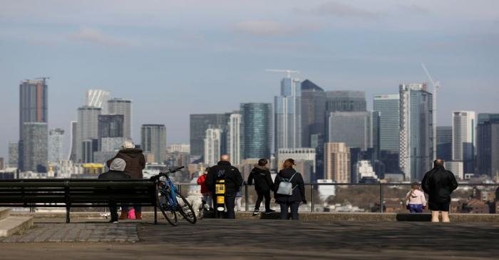 FILE PHOTO: People look out onto the Canary Wharf district as they walk through Greenwich Park