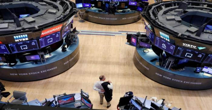 A trader puts on his jacket on the floor of the New York Stock Exchange (NYSE) as the building