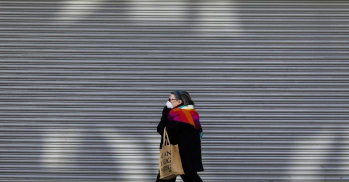 A woman walks past a shuttered shop in London