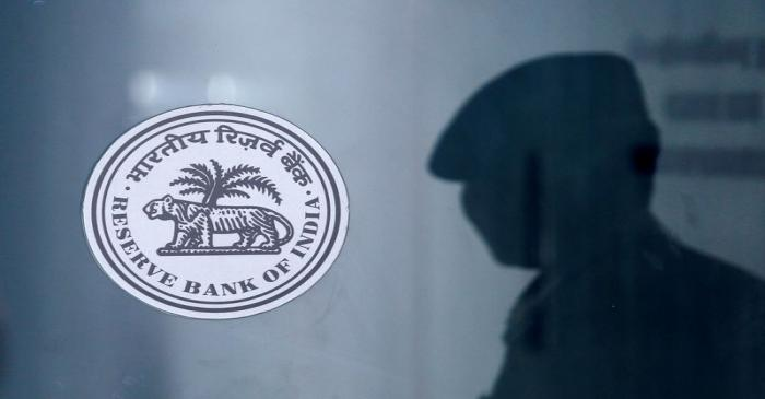 A security guard's reflection is seen next to the logo of the Reserve Bank Of India (RBI) at