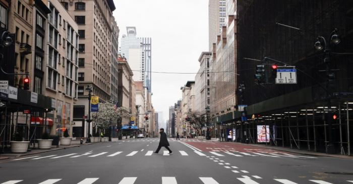 A man crosses a nearly empty 5th Avenue in midtown Manhattan during the outbreak of the