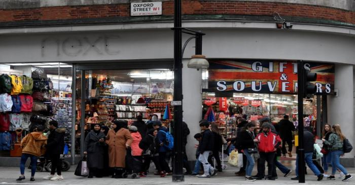Shoppers walk past a former branch of the British clothing retailer Next, now converted into an