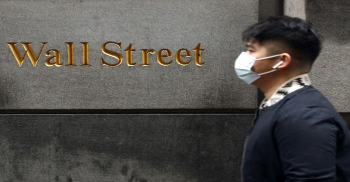 A man wears a protective mask as he walks on Wall Street during the coronavirus outbreak in New