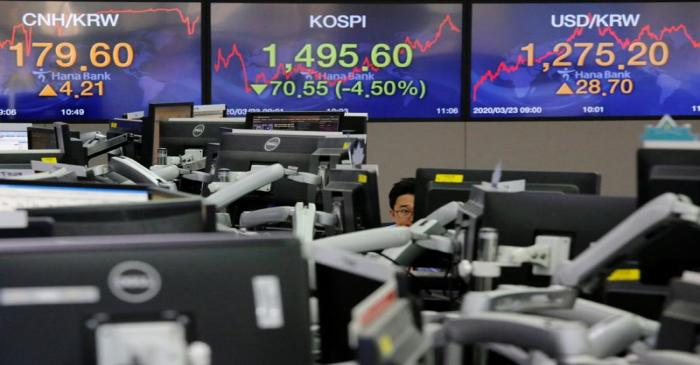 A currency dealer works in front of electronic boards showing the Korea Composite Stock Price