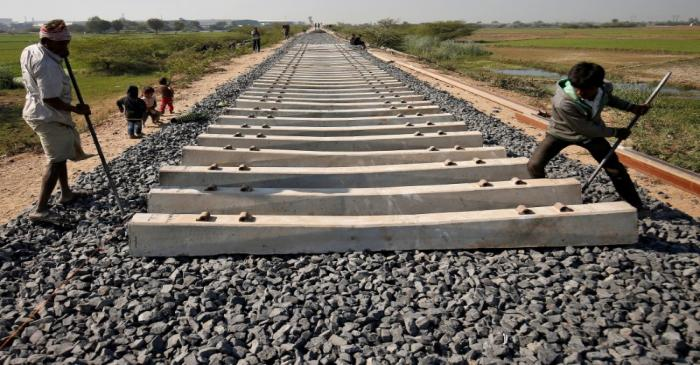 FILE PHOTO: Labourers build a new railway track on the outskirts of Ahmedabad