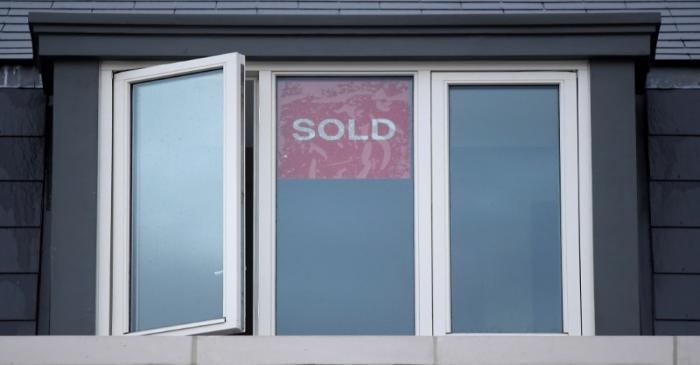 FILE PHOTO: Property sold signs are seen on windows of a group of newly built houses in west
