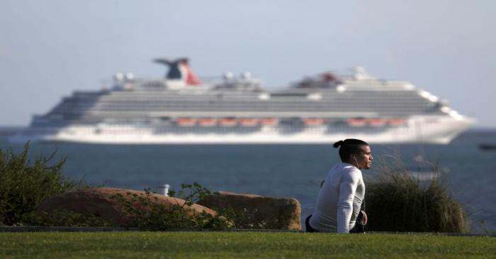 A person stretches at a park overlooking the Pacific Ocean and Carnival Panorama cruise ship as