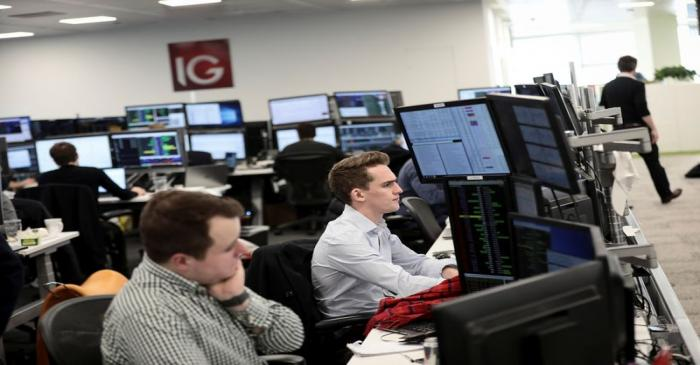 FILE PHOTO: Traders look at financial information on computer screens on the IG Index trading
