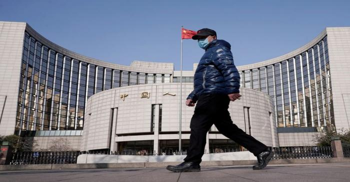 Man wearing a mask walks past the headquarters of the People's Bank of China, the central bank,