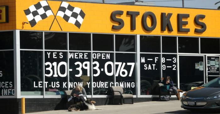 People wait outside a newly-reopened tire store, as the global outbreak of the coronavirus