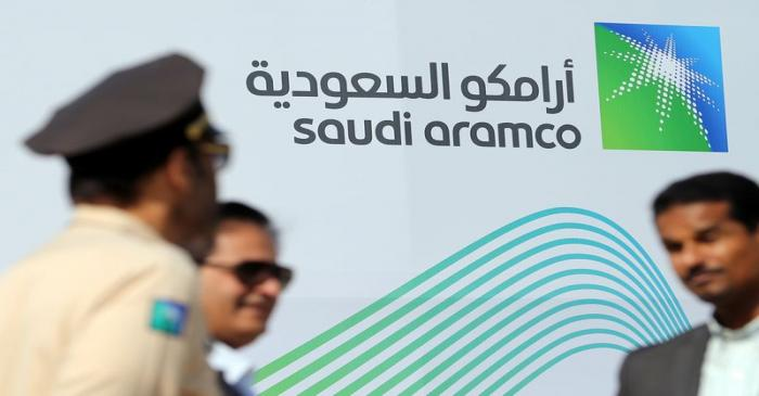 Logo of Aramco is seen as security personnel stand before the start of a press conference by
