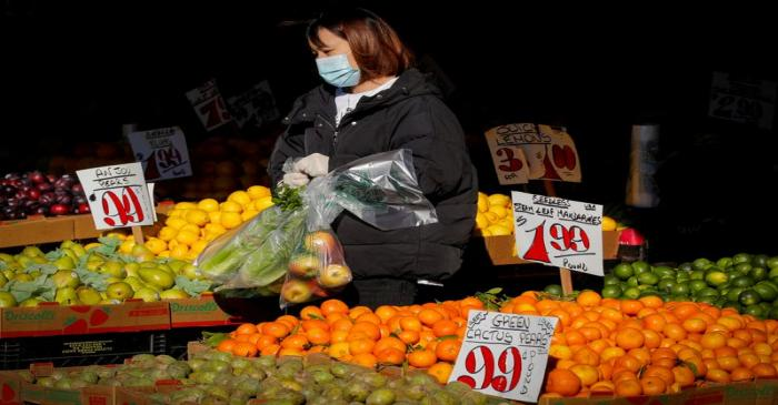FILE PHOTO: A woman wears a mask and gloves as he shops at a fruit stand, during the outbreak