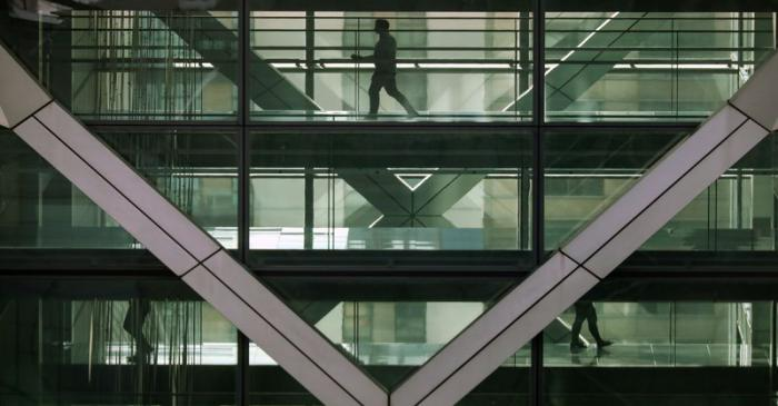 People walk in an office in the financial centre of Canary Wharf