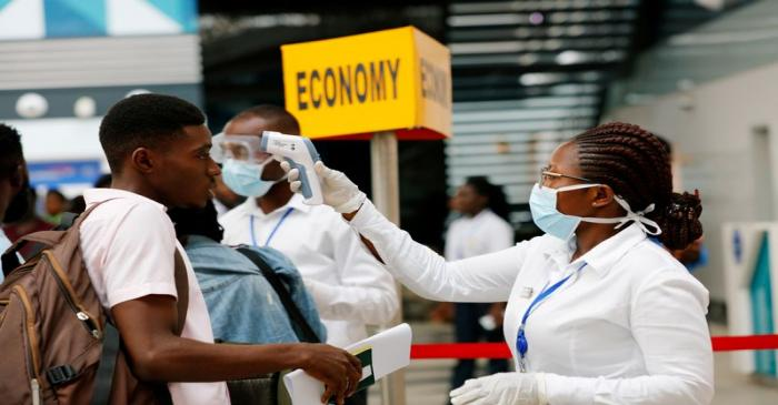 FILE PHOTO: A health worker checks the temperature of a traveller as part of the coronavirus