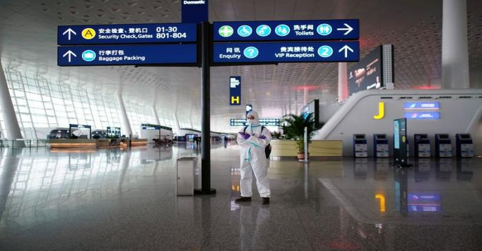 Man in protective suit stands at Wuhan Tianhe International Airport in Wuhan