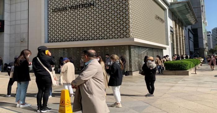 People queue to enter the Chanel boutique at a department store amid the coronavirus disease