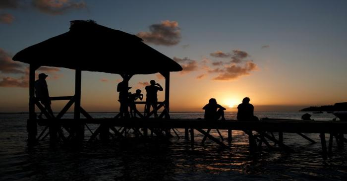 FILE PHOTO: People look at the sunset from the beach in Bel Ombre