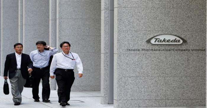 People walk past the new headquarters of Takeda Pharmaceutical Co in Tokyo