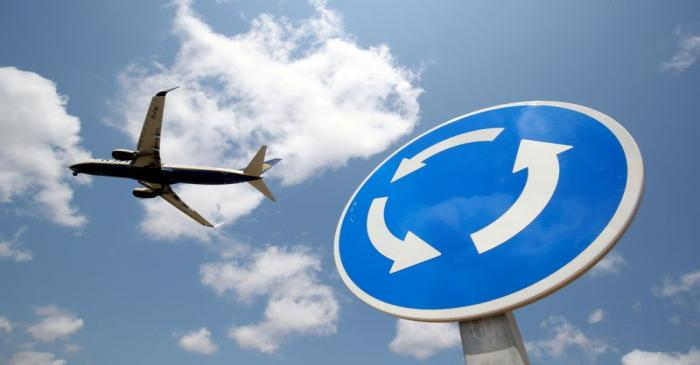 FILE PHOTO: A Ryanair Boeing 737 airplane passes a roundabout sign as it lands at Barcelona-El