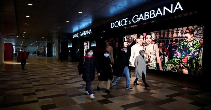 People wearing face masks walk past a Dolce & Gabbana store at a shopping mall in Wuhan