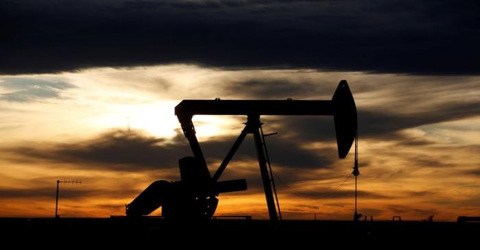 FILE PHOTO: The sun sets behind a crude oil pump jack on a drill pad in the Permian Basin in