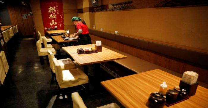 A waitress wearing a protective mask cleans a table at Toshirhin restaurant in Tokyo