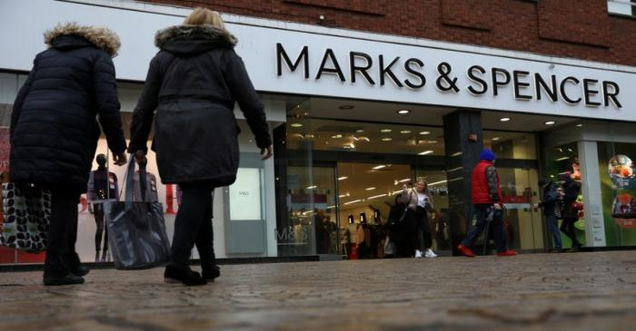 FILE PHOTO: Shoppers walk past a branch of Marks and Spencer in Altrincham, Britain