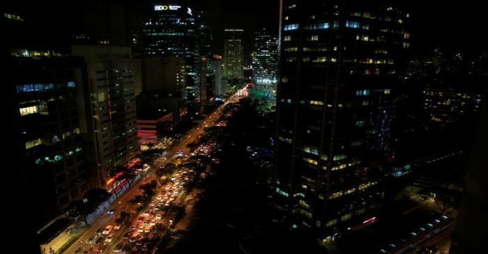 Buildings are seen as vehicles pass through the financial district of Makati city, metro Manila