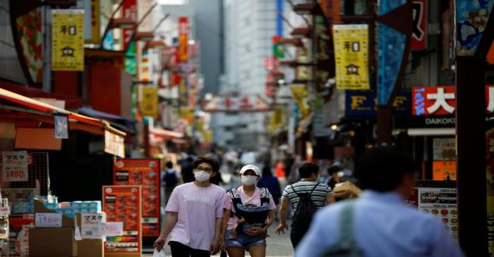 Passersby wearing protective face masks walk on the street as the spread of the coronavirus