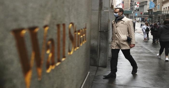FILE PHOTO: A man wears a protective mask as he walks on Wall Street during the coronavirus