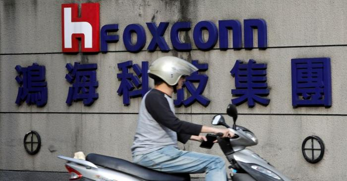 FILE PHOTO: A motorcyclist rides past the logo of Foxconn, the trading name of Hon Hai