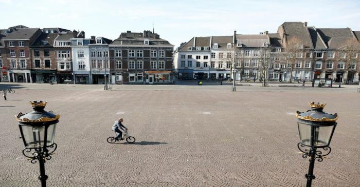 A cyclist crosses an empty square in central Maastricht