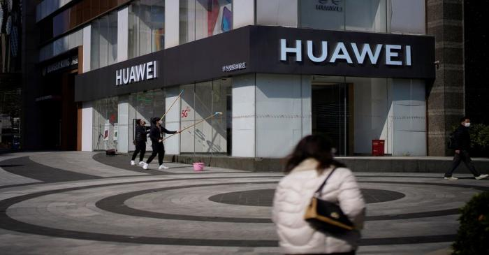 FILE PHOTO: People wearing face masks are seen at a Huawei shop on a street as the country is