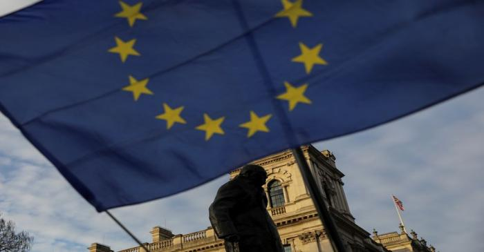 An European Union flag flies outside the Houses of Parliament in London near the statue of