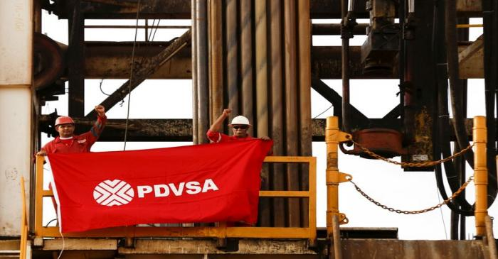 FILE PHOTO: Oilfield workers hold a flag with the corporate logo of Venezuela's state oil