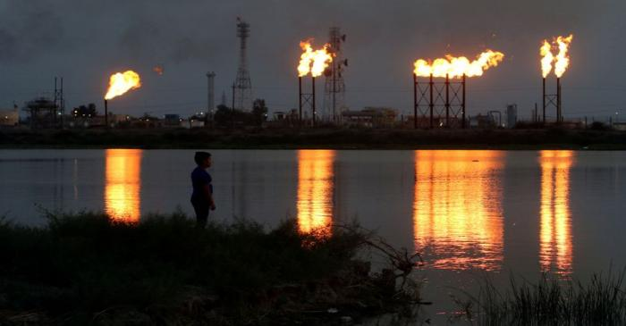 FILE PHOTO: Flames emerge from flare stacks at Nahr Bin Umar oil field, north of Basra