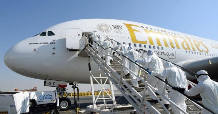 Members of cleaning staff in protective suits board an Emirates Airbus A380 to disinfected it