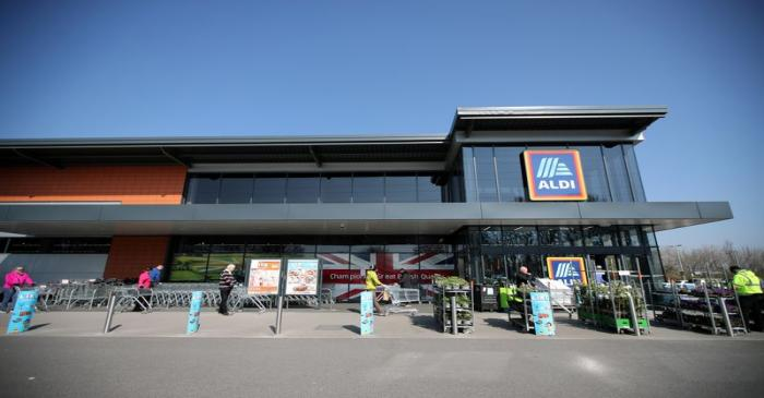 FILE PHOTO: People follow social distancing rules while they queue outside an Aldi store in