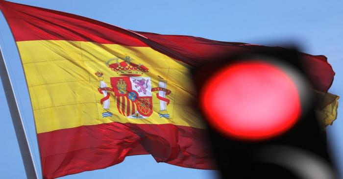 A Spanish flag flutters behind a red traffic light in Madrid