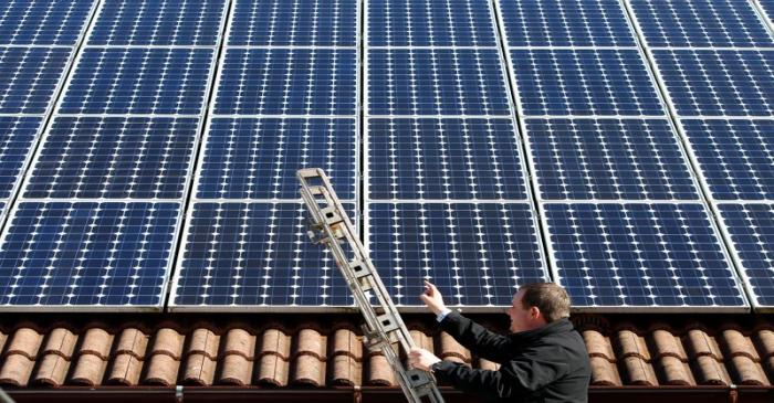 Michael Greif controls his 56 photovoltaic (solar) panels at the roof of his house in Coburg