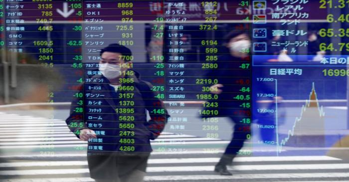 Passersby wearing protective face masks are reflected on a screen displaying stock prices