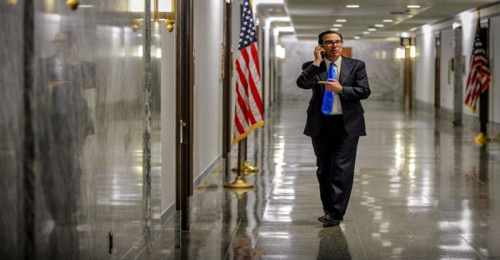 Treasury Secretary Steve Mnuchin takes a phone call in the hall outside a meeting to wrap up