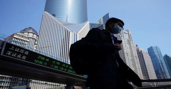Pedestrian wearing a face mask walks near an overpass with an electronic board showing stock