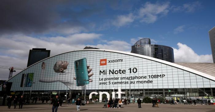 FILE PHOTO: Pedestrians walk past an advertisement for Xiaomi Mi Note 10 smartphone at the