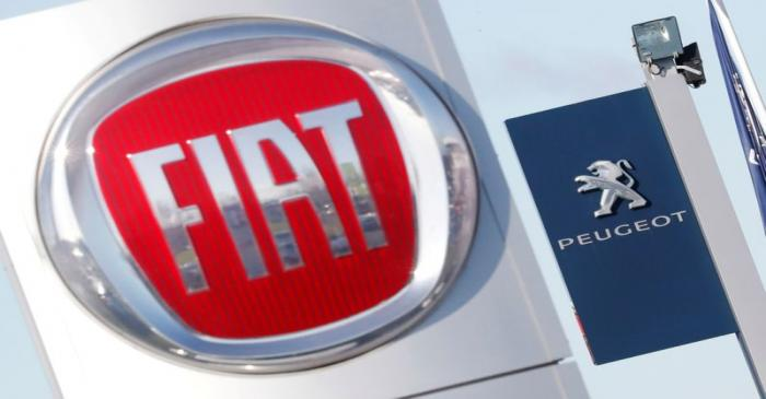 FILE PHOTO: The logos of car manufacturers Fiat and Peugeot are seen in front of dealerships of