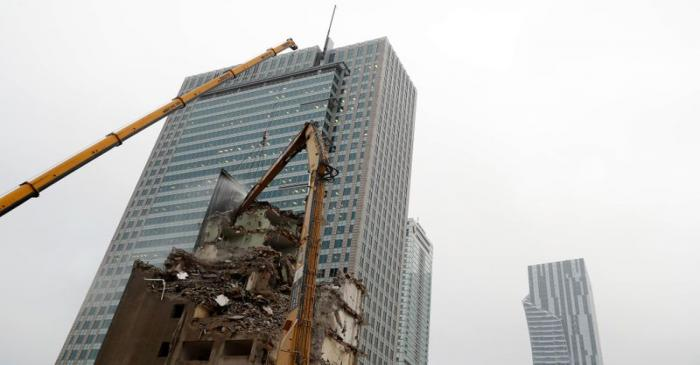 An excavator demolishes a building near skyscrapers in the centre of Warsaw