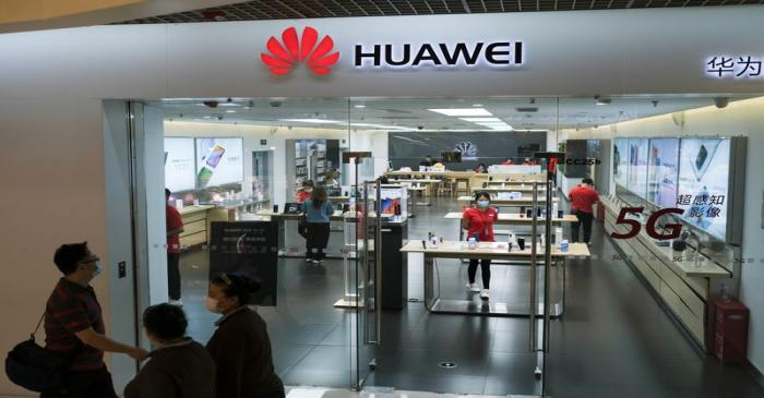 People wearing face masks walk past a?Huawei?store at a shopping mall, following an outbreak of