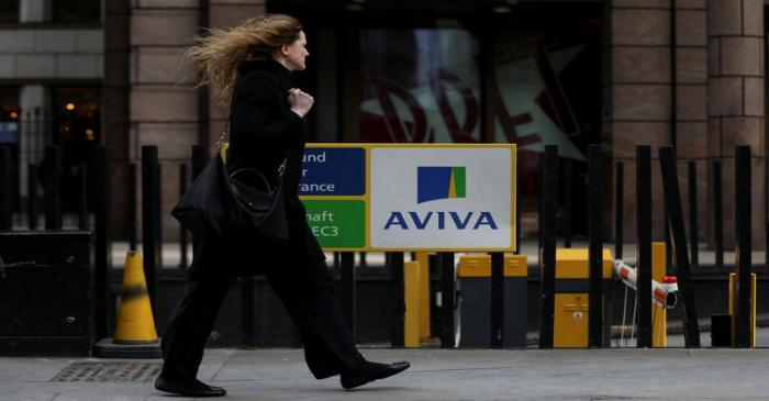 FILE PHOTO: A pedestrians walks past the Aviva logo outside the company head office in the city